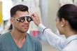 ophthalmologist measuring mans eye vision