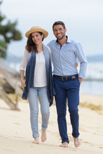 Mid-adult Couple Walking Barefoot Along The Beach