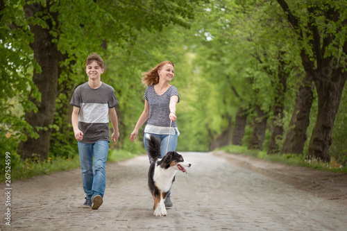 Obraz na plátne  Happy family - mom and son, walking with dog
