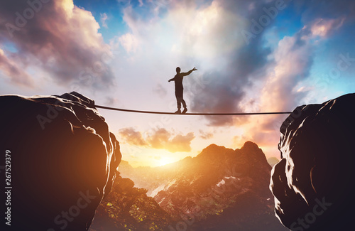 Fotografia Man walking on rope between two high mountains