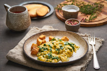 Scrambled Eggs With Spinach, Cup Of Tea On Dark Brown Background. Breakfast With Pan-fried Omelette, Side View, Close Up