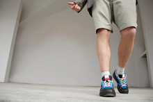 A Man In Shorts And Sneakers Goes On A Marble Tile. Close-ups Of Sneakers On The Background Of A Gray Wall.