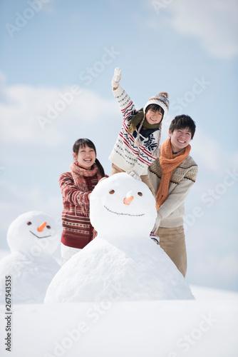 Obraz na plátně  雪だるまの側で微笑む家族