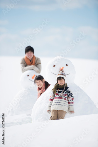 Fototapeta  雪だるまの側で微笑む家族