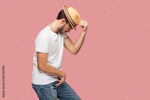 Fototapeta Profile side view portrait of bearded young dancer man in white shirt holding his hat and standing in michael jackson dancing pose
