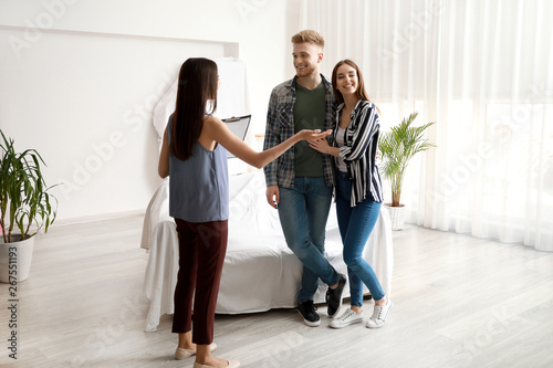 Photo  Real estate agent showing young couple a new house
