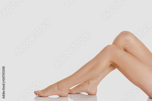 Woman legs while sitting on white background. Depilation concept. Tableau sur Toile