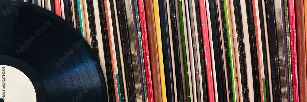 Fototapeta Vinyl record in front of a collection of albums, vintage music concept