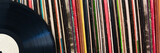 Vinyl record in front of a collection of albums, vintage music concept