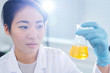 Leinwandbild Motiv Serious puzzled young Asian laboratory worker in rubber gloves standing in sunlight and examining chemical liquid in flask