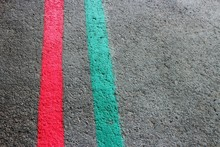 Grey Uneven Textured Surface And Stripes Painted In Red And Green.