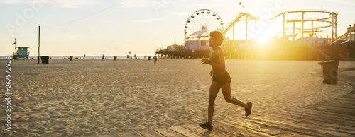 athletic african american woman jogging on boardwalk at sunset Wallpaper Mural