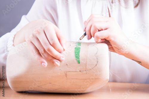 Dłonie młodej kobiety robiącej sztuczne wąsy.