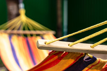 Ropes And Wooden Detail Of A Hammock, Against The Background Of Multi-colored Fabric.