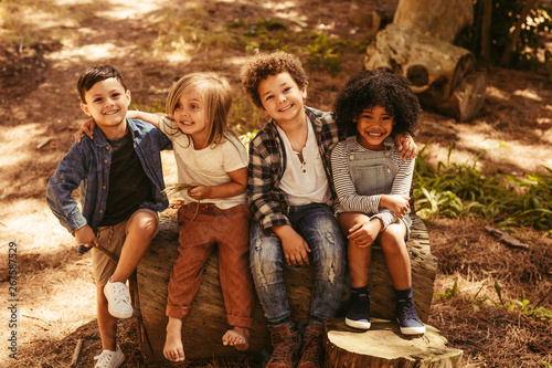 Fototapety, obrazy: Group of kids on a wooden log