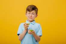 Beautiful Boy Taste A Fresh Lime Taste Sour Grimace, Facial Emotions Negative, In Blue T-shirt, Isolated Yellow Background, Copy Space