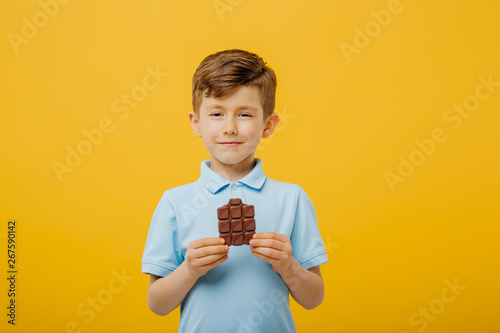 beautiful little boy tasting chocolate, look at the camera, in blue T-shirt, isolated yellow background, copy space
