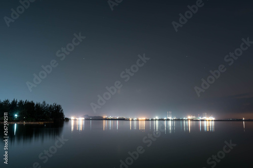 Aluminium Prints Dark grey Coastline view of sea, pier, sky during dusk with lights reflection on water