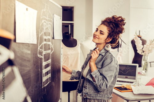 Obraz na plátně  Clothes designer looking happily at her sketches.