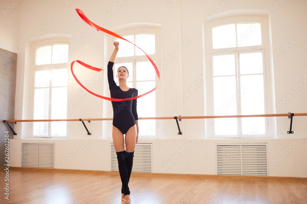 Fototapety, obrazy: Inspired elegant girl in bodysuit and stockings without toes twirling red ribbon while performing rhythmic gymnastics in studio