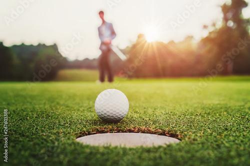 Obraz na płótnie golf player putting golf ball into hole