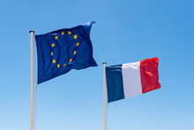 French And European Union (EU) Flag. Waving Flags Of France And Europe. Blue Sky Background.