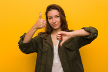 Young European Woman Isolated Over Yellow Background Showing Thumbs Up And Thumbs Down, Difficult Choose Concept