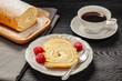 Leinwandbild Motiv Ciasto - rolada biszkoptowa z kremem mascarpone na talerzyku, obok kawa w filiżance, wszystko postawione na czarnym drewnianym blacie