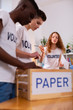 Boys and girl sorting paper while working in ecology organization