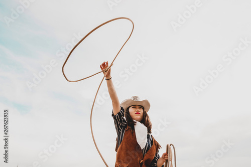 Fotografía pretty Chinese cowgirl throwing the lasso in a horse paddock