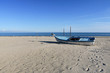 Old fishing boat left on the empty wide sandy beach, quiet afternoon on Katerini Beach, Greece