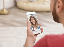Young Man Using Video Chat On Smartphone At Home, Closeup. Space For Design