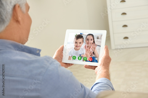 Fototapeta  Closeup view of senior man talking with grandchildren via video chat at home