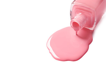 Spilled color nail polish with bottle on white background