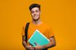 Leinwandbild Motiv Young student man holding books smiling and raising thumb up