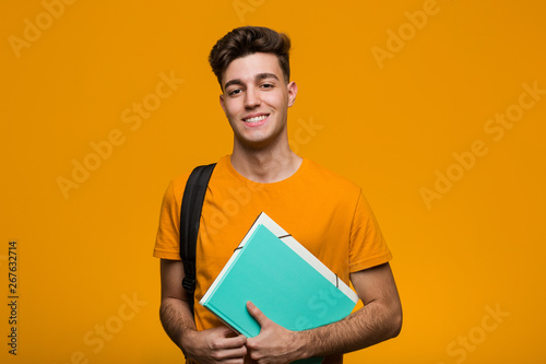 Young student man holding books smiling and raising thumb up Wallpaper Mural
