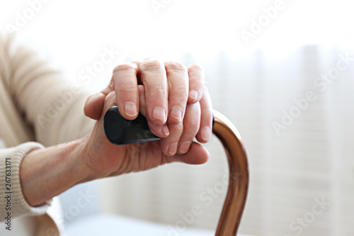 Elderly woman sitting in nursing home room holding walking quad cane with wrinked hand Fototapet