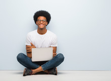 Young Black Man Sitting On The Floor With A Laptop Crossing Arms, Smiling And Relaxed
