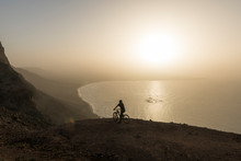 Spain, Lanzarote, Mountain Biker On A Trip At The Coast At Sunset Enjoying The View