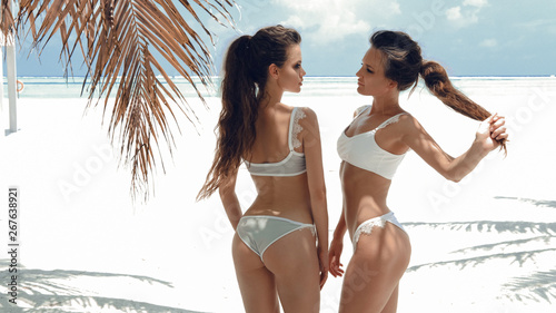 Outdoor photo of two sexy bikini girls models in fashion swimsuits on tropical beach at Maldives island Canvas Print