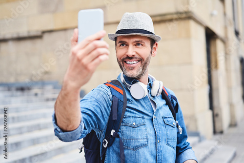 Foto  Tourist taking selfie with smartphone while sightseeing in the city