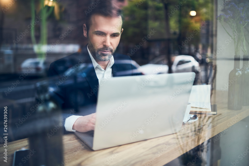 Fototapeta Handsome businessman working on laptop and sitting in cafe