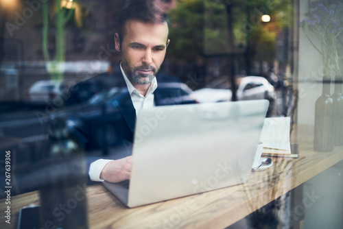 Handsome businessman working on laptop and sitting in cafe - 267639306