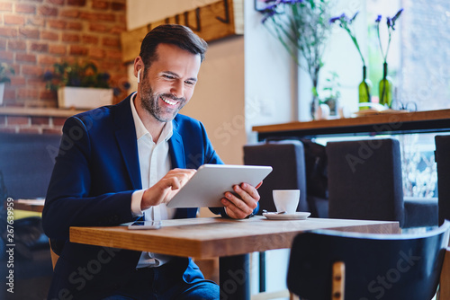 Obraz Businessman sitting in cafe using tablet and talking through wireless headphones - fototapety do salonu