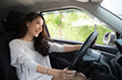 Leinwandbild Motiv Asian women driving a car and smile happily with glad positive expression during the drive to travel journey, People enjoy laughing and relaxed happy woman on road trip vacation concept, Thai model