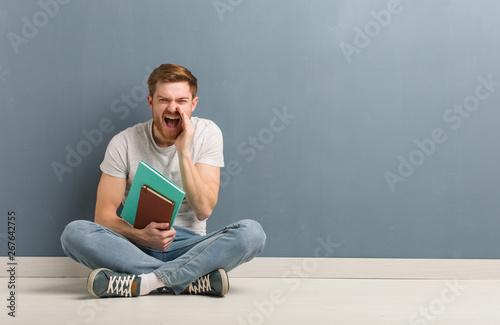 Young redhead student man sitting on the floor shouting something happy to the front Poster Mural XXL