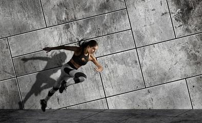 Woman running on sidewalk. Urban background