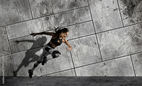 obraz lub plakat Woman running on sidewalk. Urban background