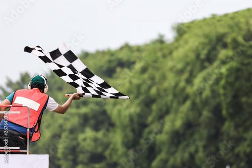 Obraz na plátně Back view of man holding checkered race flag