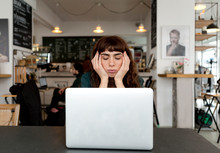 Frustrated Young Woman Using Laptop In A Cafe